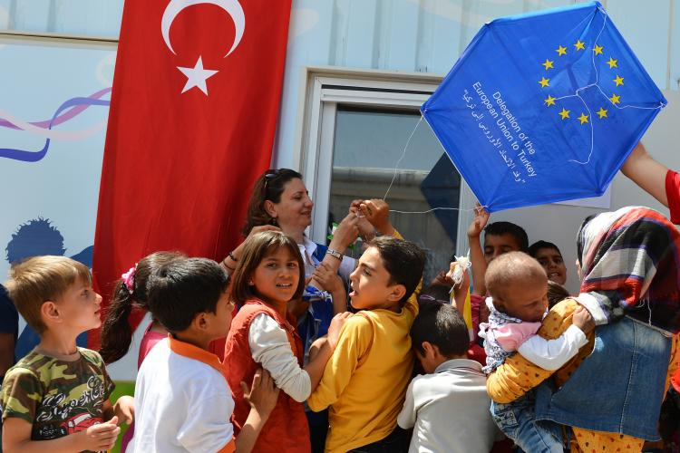 Young syrian migrants in the Harran camp with Turkish flag and EU kite