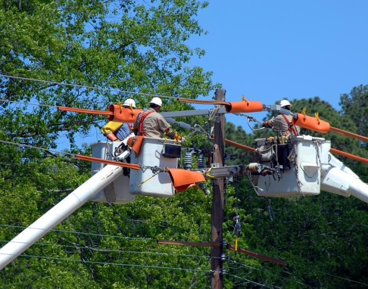 Three buckets trucks lift linemen to top of electricity pole. Three repairmen combine knowledge and repair power outage.