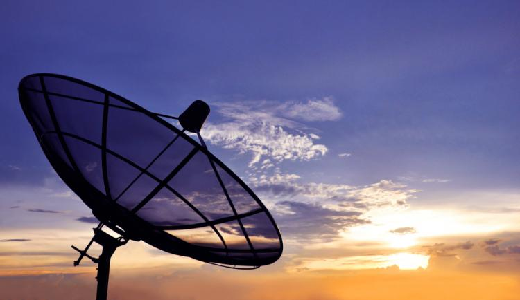 A black satellite dish on twilight sky background