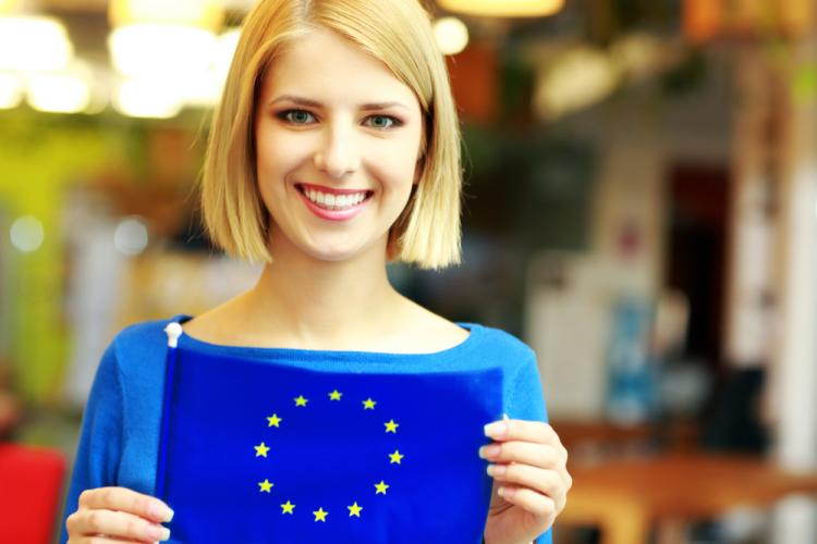 A blonde female student holding the EU flag