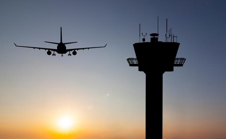 plane landing at sunset and a control tower