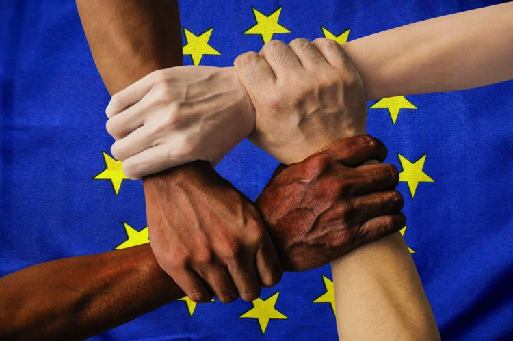 Multi ethnic hands in front of the EU flag